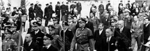 Le Général von Stülpnagel (Militärbefelshaber en France), Fernand de Brinon (ambassadeur en France), suivi de Pierre Laval, et l'ambassadeur Scapini (à l'extrême droite) accompagné de son guide, font leur entrée au Grand Palais.